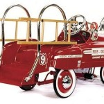 "Deluxe Fire Truck Classic Pedal Car! Inspired by the famous and highly collectible ""sad face"" pedal Fire Truck of the 1940's, it is true in its details. There is no tailgate, but a rear step just like the original. This deluxe model comes in a deep red color and is highlighted with white graphics."
